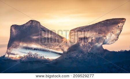 Beautiful transparent ice of Lake Baikal against the dark blue orange sky and a bright sun. russia