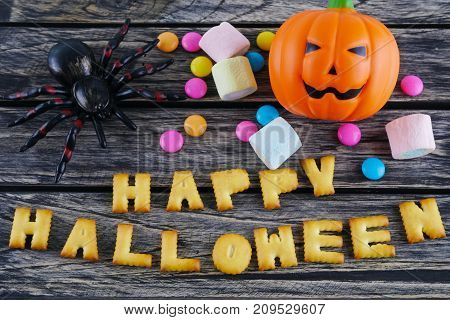 Happy Halloween words decoration with scary spider candy and jack lantern pumpkin on wooden background
