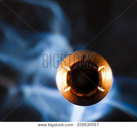 Copper plated hollow point bullet with smoke coming at the viewer
