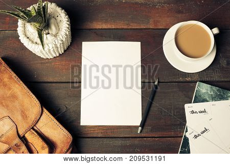 Opened craft paper envelope , autumn leaves and coffee on rustic wooden table
