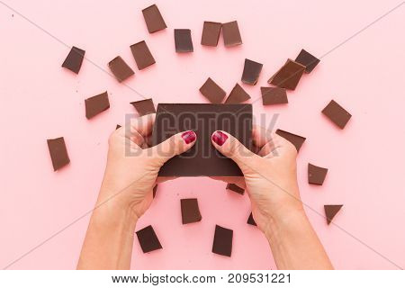 Top view on woman's hands breaking a piece of dark chocolate above pink table background.