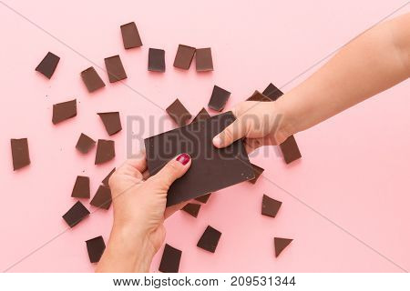 Top view on child's hand taking a broken piece of chocolate from mother's hands above pink table background.
