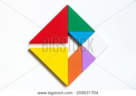Colorwood tangram puzzle on square with arrow sign shape on white background (Concept of Business direction company vision or target)