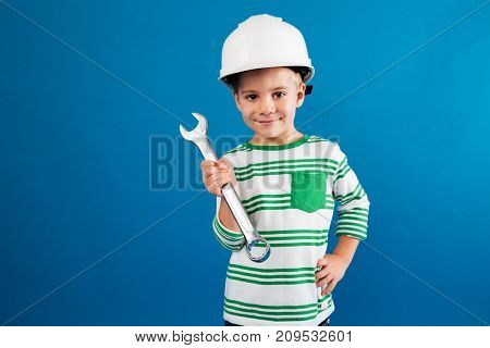 Smiling young boy in protective helmet posing with wrench like engineer and looking at the camera over blue background