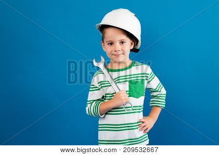 Cheerful young boy in protective helmet posing with wrench like engineer and looking at the camera over blue background