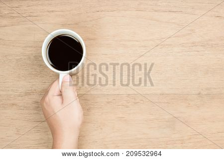 yellow brown hand hold white coffee cup on wood texture from top view left hand side empty area for copy space