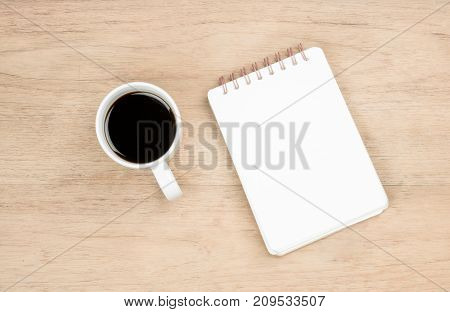white opened notebook and white coffee cup place on brown wood texture from top view