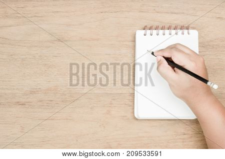 brown skin hand use black pencil writing on white page of small notebook place on wood texture empty area on left of image for copy space and thinking time concept from top view