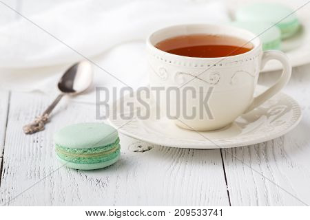 Cup Of Tea And Macaroons On Vintage Pastel Background