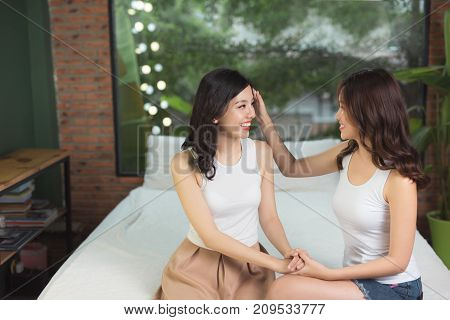 Relaxed young female friends chatting in bed room