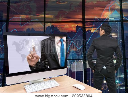 the computer on the wood table with Businessman point sign of money at the screen in front of the glass window over on the trading graph over the blurred photo of cityscapeBack side of Businessman