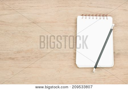 opened page of small notebook and black pencil place on wood texture