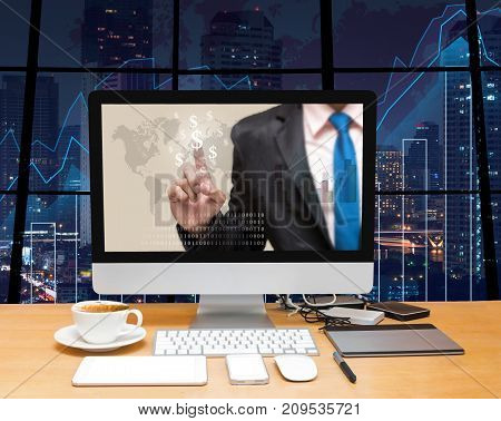 Workspace with computer desktop with Businessman point sign of money at the screen on the trading graph over the blurred photo of cityscape backgroundElements of this image furnished