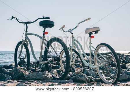 Two city bikes on the beach in the morning