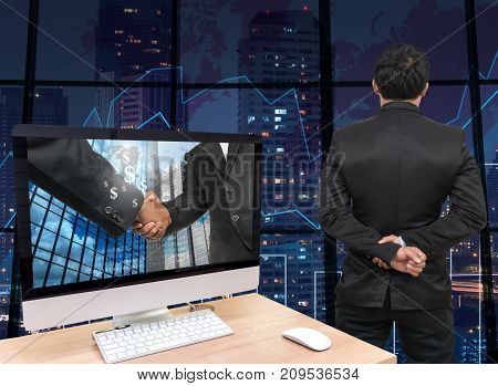 the computer on the wood table with Hand shake between businessman at the screen in front of the glass window over on the trading graph over the blurred photo of cityscapeBack side of Businessman