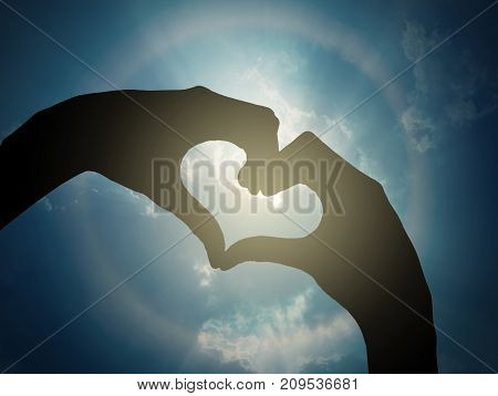 two hands making a heart shape on sun corona with cloud over the blue sky background valentine love concept