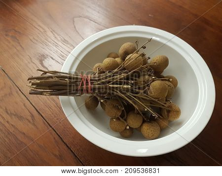 Close-up view of a bunch of tropical Asian longan fruit also known as Dragon eyes in Chinese set a white bowl on wooden table