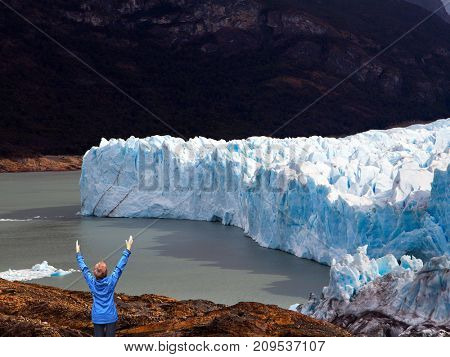 Patagonia. The concept of  exotic and extreme tourism. Unique lake and glacier Perito Moreno,  in a mountain valley. Woman -  tourist enthusiastically raised her hands
