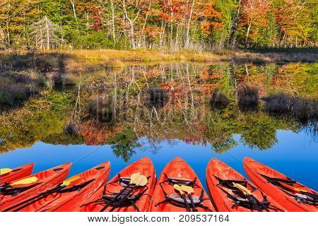 Foliage of autumn forests is reflected in pond. Picturesque red canoes moored on the lake. Magnificent resort Mont Tremblant. Concept of ecological tourism