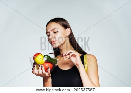 the dissatisfied young girl is hungry, sits on a diet, holds a plate with vegetables and fruits in her hands