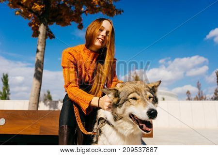 red-haired girl smiles, sits on a wooden bench with her big gray dog