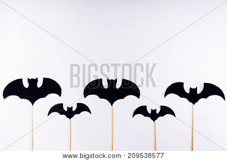 on white background, painted black bats on wooden sticks