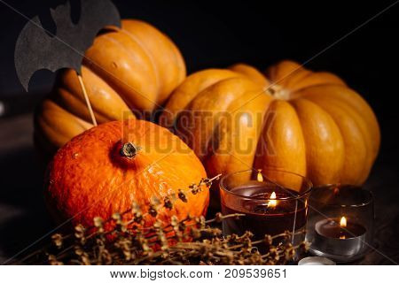 composition for decorating a house for halloween, yellow and orange pumpkins, burning scented candles