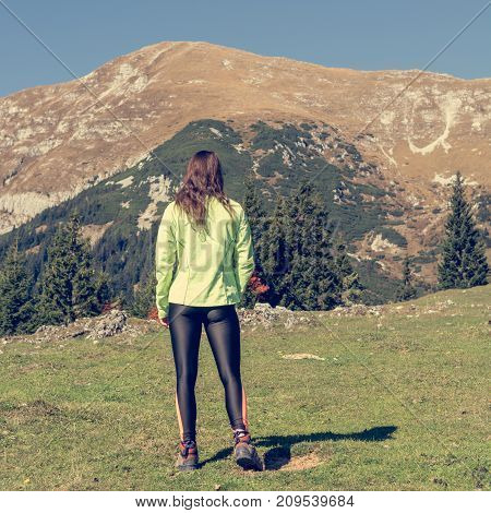Attractive brunette posing in mountains. Female athlete on mountain meadow.