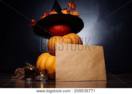 composition for decorating a house for halloween, yellow and orange pumpkins, burning aromatic candles, a big black witch hat