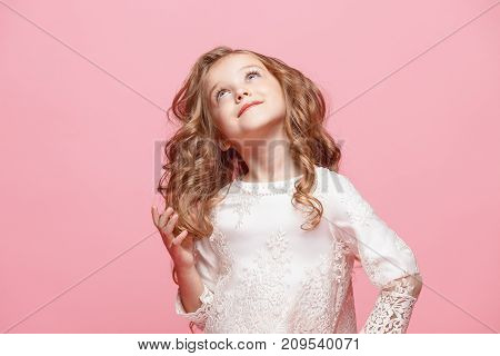 The beautiful little girl in long dress standing and posing over pink background