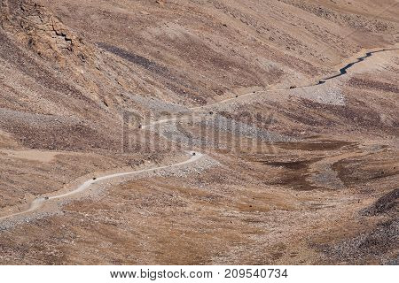 Landscape image of mountains and cars on the road in Ladakh India