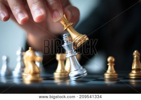 Close up shot hand of business woman moving golden chess to defeat and kill silver king chess on white and black chess board for business challenge competition winner and loser concept selective focus on king chess shallow depth of field