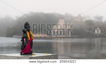 Hindu staue in a famous temple (Grand Basin) background templein the day with mist for create mystical atmosphere.Mauritius