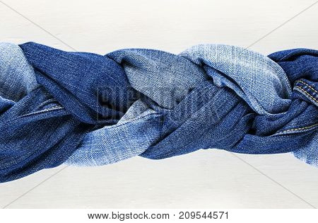 stylish woven braid of blue jeans on a white wooden background