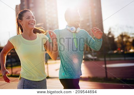 Young attractive and cheerful couple running outside on sunny day