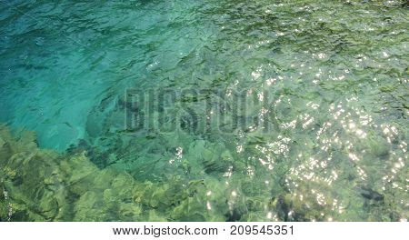 Turquoise natural sea water color background, waves and glare