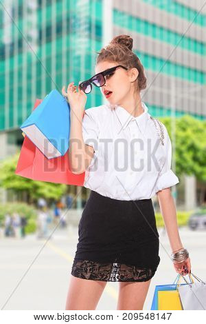 Young woman with colorful shopping bags standing in the street
