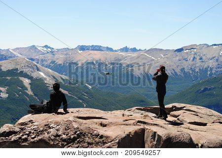 Couple of people doing bird watching / Condor flying near by / Two persons watching a bird on the top of a mountain