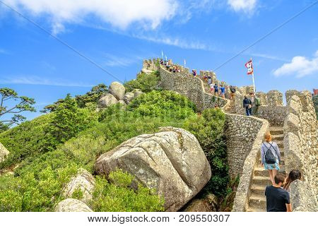 Sintra, Portugal - August 7, 2017: close up of many tourists walking over defensive walls in one of Sintra's most popular attraction. Castle of the Moors is a medieval castle and Unesco Heritage.