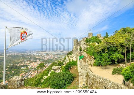 Aerial view of ancient wall and tower of Castle of the Moors and Sintra valley. Castelo dos Mouros is medieval castle and Unesco Heritage on a hill above Sintra, Lisbon District, Portugal.