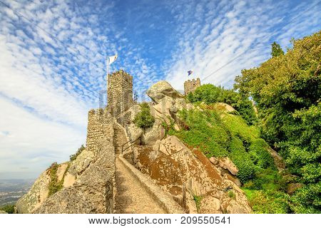 The ancient wall and tower of ruins of Castle of the Moors. The Moorish fortress is a medieval castle and Unesco Heritage on top of a hill above Sintra, Lisbon District, Portugal.
