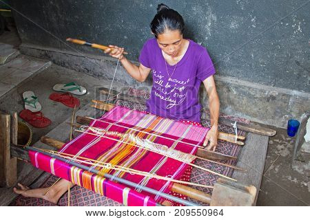 LOMBOK, INDONESIA - DECEMBER 30, 2016: Woman weaving on a loom in Lombok on 30th december 2016