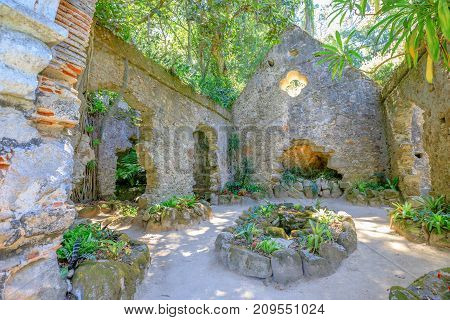 Ruins of chapel covered by vegetation in Monserrate Park, on the hills above Sintra, Lisbon, Portugal, Europe.