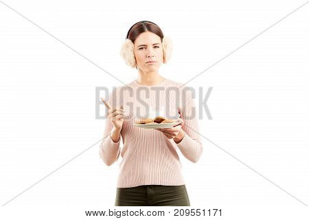 Studio portarit of young woman in earmuffs holding plate with biscuits