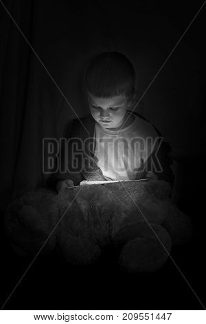 Funny boy sitting with a tablet in the dark before bed time in artistic conversion