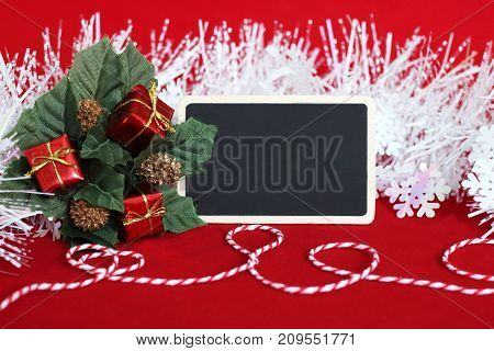 A rectangular blank slate to write a message, leaves filled with red gifts, a frosted white wreath and a red and white thread for holiday decorations
