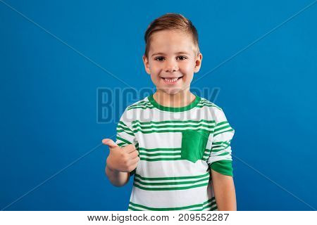Portrait of a happy kid showing thumbs up gesture isolated over blue background