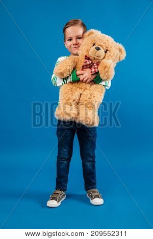 Full length portrait of a lovely little boy hugging teddy bear and looking at camera isolated over blue background