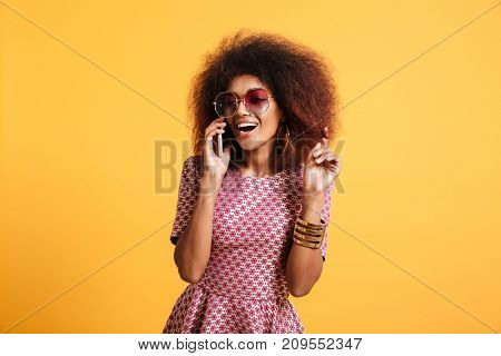 Portrait of a happy cheerful afro american woman in retro style clothes talking on mobile phone while standing isolated over yellow background