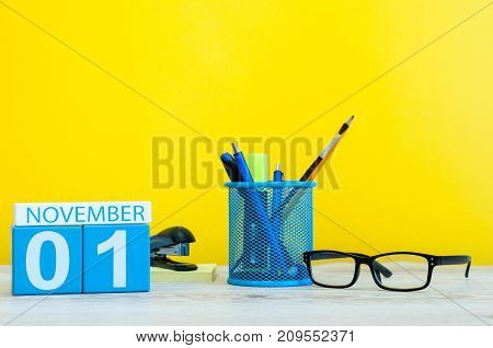 November 1st. Day 1 of month, wooden color calendar on yellow background with office supplies. Autumn time.